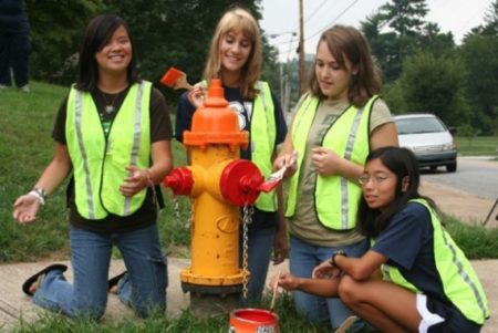 girl scouts painting fire hydrant