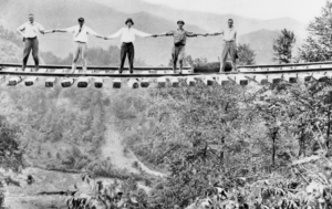 Men stand aloft on a railroad bridge in McDowell County after its center supports had been washed away during the Flood of July 1916. (Photograph courtesy of the State Archives of North Carolina)