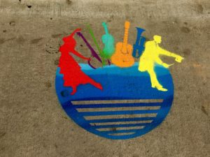 This symbol painted on downtown sidewalks identifies the two high-impact areas in the street performer pilot program. These include around the Flat Iron sculpture on Wall Street at Battery Park Avenue and the Haywood Street sidewalk in front of Woolworth Walk.