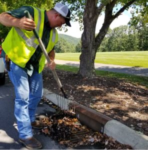 Public Works employees are clearing drains of debris in advance of the storm, to ensure that water flows into stormwater systems. This helps prevent street flooding. Shown here is Terry Manos.
