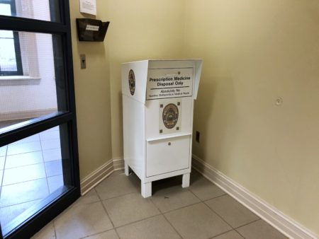 Photograph of the chest-high white prescription medicine drop-off bin in the lobby of the police department.